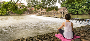 a woman meditating on a pink blanket looking out over moving water