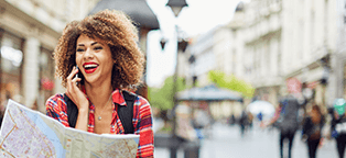 Femail tourist on cell phone smiling with map in hand unaware of surroundings