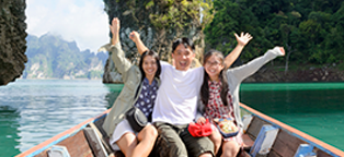Man sitting in between wife and daughter on boat in lake all smiling with open arms in air