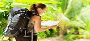 woman by herself walking through terrain looking at map