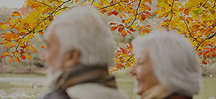 senior man and woman taking a walk in the fall foliage