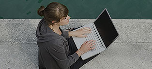 Woman outside typing on laptop