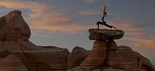 lady doing yoga on top of rock at famous rocky landmark