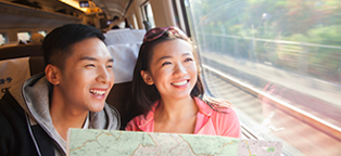 young man and woman on train holding map smiling while looking out of the window