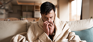 Man wearing robe and sneezing into a tissue sick with the flu